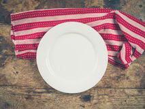 White plate and tea towel on wooden table Royalty Free Stock Images