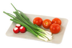 White plate with tomato, radish and green onion. Vegetarian food Royalty Free Stock Photography