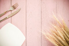 White plate, vintage fork and knife  on rustic pink wooden table. Royalty Free Stock Photos