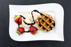 White plate with waffle, ice and strawberries decorated with chocolate stripes on a dark slate Royalty Free Stock Photography