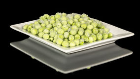 White plate willed with frozen green peas Stock Photos