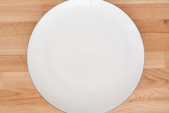 White plate. On wooden background Stock Photo