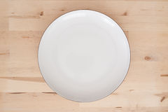 White plate. On wooden background Stock Photos