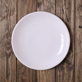 White plate. On a wooden background Stock Photo