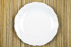White plate on a wooden background Royalty Free Stock Image