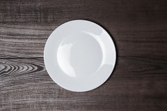White plate on wooden brown table Royalty Free Stock Photos