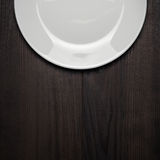 White plate on wooden brown table Royalty Free Stock Images