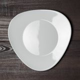 White plate on the wooden brown table Stock Image