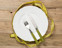 White plate on the wooden desk with knife and fork wrapped with Royalty Free Stock Photos