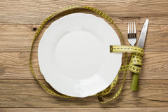 White plate on the wooden desk with knife and fork wrapped with Stock Image