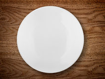White plate on wooden table Royalty Free Stock Image