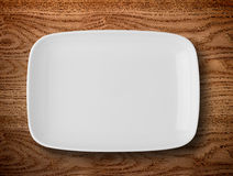 white plate on wooden table Stock Images