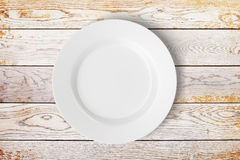 White plate on wooden table Royalty Free Stock Photography