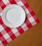 White plate on wooden table with red tablecloth stock photos