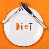 White plate with word diet made of pieces of vegetables on orange tablecloth background. Fork and knife lying on it. Royalty Free Stock Photography