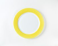 White plate with yellow rim Royalty Free Stock Photography