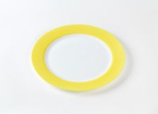 White plate with yellow rim Royalty Free Stock Images
