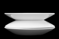 White plates. Isolated on black background Stock Photos