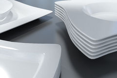 White plates. Stacks of elegant white plates and bowls with wavy edges on a black surface Royalty Free Stock Photography