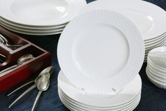 White plates. Stack of white dishes and tea spoons stock images