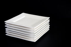 White Plates on Black. Contemporary square white plates stacked against a dark black background stock images