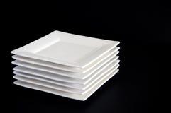 White Plates on Black stock images