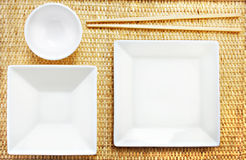 White Plates and Chopsticks on a Bamboo Mat Royalty Free Stock Image
