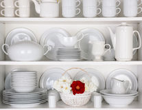White Plates in Cupboard With a Basket of Roses. Closeup of white plates and dinnerware in a cupboard. A basket of white and red roses is centered on the bottom royalty free stock images