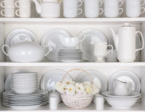 White Plates in Cupboard. Closeup of white plates and dinnerware in a cupboard. A basket of white roses is centered on the bottom shelf. Items include, plates royalty free stock images