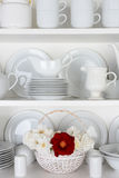White Plates in Cupboard and One Red Rose Stock Photography
