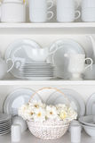 White Plates in Cupboard With Roses. Vertical closeup of a basket of roses on the shelf of a cupboard full of white plates. Items include, plates, saucers, bowls royalty free stock photography