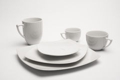 White plates and cups. Over the white Royalty Free Stock Photography