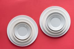 White plates of different sizes. On red background stock photo
