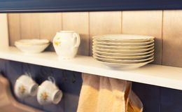 White plates and dinnerware in a cupboard. Picture of white plates and dinnerware in a cupboard stock image