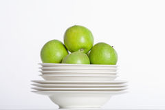 White plates and green apples Royalty Free Stock Photos