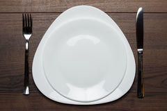 White plates with knife and fork on wooden table Royalty Free Stock Photos