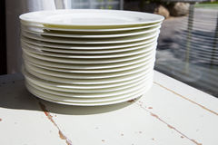 White plates piled close to window Royalty Free Stock Images