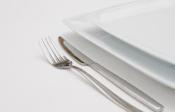 White plates with silver fork and knife Stock Photography