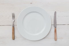 White plates and silverware on a light wood Royalty Free Stock Image