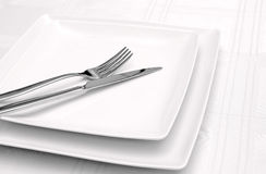 White plates on white tablecloth Stock Photos