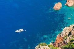 White pleasure boat anchored near rocky coast Stock Image