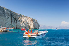White pleasure boat floating on sea water. Zakynthos, Greece - August 20, 2016: White pleasure motor boat floating on sea water near rocky island coast in summer Royalty Free Stock Photos