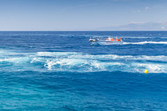 White pleasure boat goes on sea water, Greece. Zakynthos, Greece - August 20, 2016: White pleasure boat goes on sea water in summer day Royalty Free Stock Photography