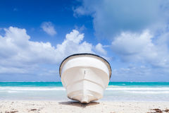 White pleasure boat lays on sandy beach Stock Images