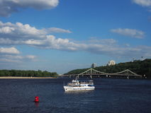 A white pleasure boat with passengers aboard sailed along the center of the river in Kiev. In the background a pedestrian suspension bridge. Summer sunny Stock Images