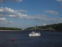 A white pleasure boat with passengers aboard sailed along the center of the river in Kiev. In the background a pedestrian suspension bridge. Summer sunny Stock Photo