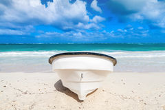 White pleasure motor boat lays on sandy beach. Front view Royalty Free Stock Photo