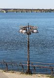 white plofony in metal sculpture with a lamppost with a background of blue river and bridge stock photos