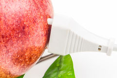 White plug is connected to the red apple on white background Stock Images