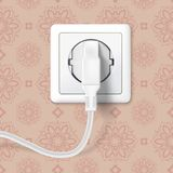 White plug inserted in a wall socket on backdrop of wall with wallpaper. The plug is plugged into the power lines with. Electric cord. Icon of device for Royalty Free Stock Image